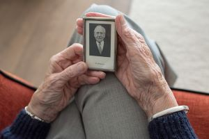 elderly lady holding a picture of her husband